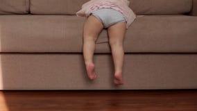 Risos e corrediças bonitos pequenos do bebê do sofá macio a pavimentar no movimento lento video estoque