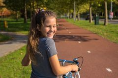 Risos holandeses felizes da criança A menina bonita monta a bicicleta no trajeto da bicicleta A criança do ciclista ou a menina d imagem de stock royalty free