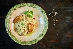 Risoto com galinha, ervilhas e tomates em uma placa de madeira, italiana Fotografia de Stock