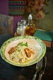 Risoto com galinha, ervilhas e tomates em uma placa de madeira, italiana Fotografia de Stock Royalty Free