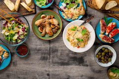 Risotto, ψημένα πόδια κοτόπουλου και πρόχειρα φαγητά σε έναν ξύλινο πίνακα Στοκ φωτογραφίες με δικαίωμα ελεύθερης χρήσης