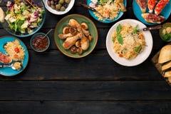 Risotto, ψημένα πόδια κοτόπουλου και πρόχειρα φαγητά στο σκοτεινό ξύλινο πίνακα Στοκ φωτογραφία με δικαίωμα ελεύθερης χρήσης