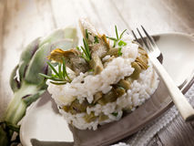Risotto with artichokes. Over dish on wood background Royalty Free Stock Photo