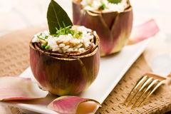 Risotto with artichokes. Stuffed artichokes with risotto on elegant table with golden fork Stock Photo
