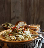 Risotto with artichokes and bacon. Top view on a wooden table Stock Photography
