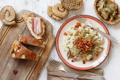 Risotto with artichokes and bacon top view. On a wooden table top view Royalty Free Stock Image