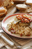 Risotto with artichokes and bacon. Top view on a wooden table Stock Photo