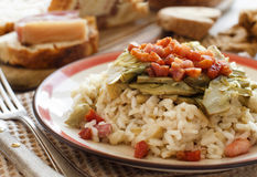 Risotto with artichokes and bacon. Top view on a wooden table Stock Image