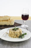 Risotto with asparagus in the ceramic plate over wooden table. With silver fork. In the background two salt focaccia pieces and a glass of red wine Royalty Free Stock Images