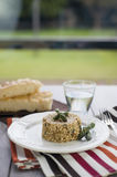 Risotto with asparagus in the ceramic plate over wooden table. With silver fork, glass of water and colored striped tablecloth. In the background two salt Stock Photo