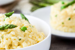 Risotto with asparagus, parsley and peas on a rustic wooden table Stock Image