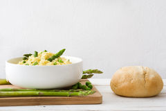 Risotto with asparagus, parsley and peas on a white wood Royalty Free Stock Photos