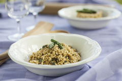 Risotto with Asparagus in two ceramic pot on purple tablecloth. With a silver fork and glasses in the background Stock Photos