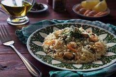 Risotto avec des crevettes d'un plat vert Images stock