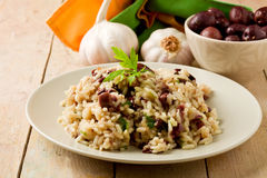 Risotto with black olives on wooden table Royalty Free Stock Images