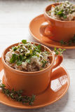 Risotto in bright orange cups. Two orange cups with risotto and herbs stock images