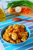 Risotto with chicken. Rice with chicken and vegetables.blue plate.national dish east.in the background of a cutting board with onions and sliced carrots Stock Photo