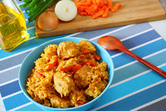 Risotto with chicken. Rice with chicken and vegetables.blue plate.national dish east.in the background of a cutting board with onions and sliced carrots Stock Photos