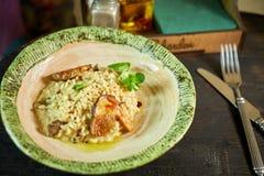 Risotto con el pollo, los guisantes y los tomates en un tablero de madera, italiano Fotos de archivo