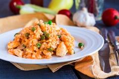 Risotto con il pollo e le verdure su un piatto con la coltelleria Fotografie Stock