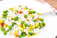 Risotto con las verduras, el maíz y los guisantes Foto de archivo