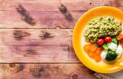 Risotto con las verduras, en fondo de madera fotos de archivo