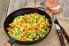 Risotto con le verdure, le carote, i piselli ed il pollo Immagini Stock