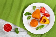 Risotto cone stuffed with meat ragu. Fried arancini - risotto cones stuffed with meat ragu, and green peas on white plate with tomato and basil leaves. tomato Royalty Free Stock Photos