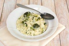 Risotto cremoso con i broccoli sul panno e sui precedenti di legno Fotografia Stock