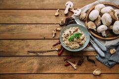 Risotto de champignon, tir de ci-dessus sur des textures rustiques foncées photos stock