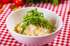 Risotto with gorgonzola, walnuts and arugula on white plate. Close up stock photography