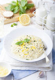 Risotto with lemon and fresh basil. White wooden background Royalty Free Stock Photo