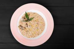 Risotto med feg lever, parmesanost, olja och vis man på plattan på svart träbakgrund royaltyfri foto