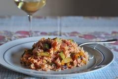 Risotto med grönsakzucchinin, gul peppar, den röda löken och någon av tomatsås med ett exponeringsglas av den pinot grigioen royaltyfria bilder
