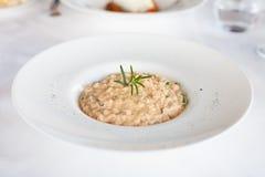 Risotto med rosmarinbladet i den vita maträtten Arkivfoto