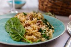 Risotto mit Pilzen und Spinat auf einer keramischen Platte stockfoto