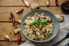 Risotto and mushroom dish in bowl. Over wooden table Stock Image