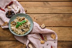 Risotto and mushroom dish in bowl over wooden table. Flat lay, top view, copy space Royalty Free Stock Photo