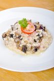 Risotto with mushrooms. Risotto with champignon mushrooms,shallot and fresh cherry tomato om the wooden desk Stock Image