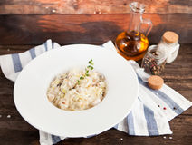Risotto with mushrooms and chicken on a white plate on a wooden Royalty Free Stock Images
