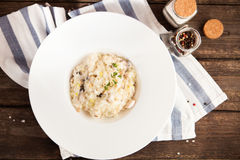 Risotto with mushrooms and chicken on a white plate on a wooden Stock Photography