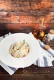 Risotto with mushrooms and chicken on a white plate on a wooden Royalty Free Stock Photography