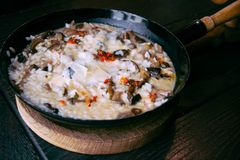 Risotto with mushrooms in cooking pan. Healthy vegetarian meal Stock Images