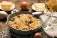 Risotto with mushrooms, fresh herbs and parmesan cheese. Wooden background. Horizontal orientation Royalty Free Stock Images