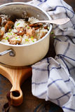 Risotto with mushrooms in pan. On cutting board Royalty Free Stock Images