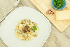 Risotto with mushrooms, parmesan cheese and parsley. On a wooden background Stock Photos