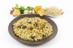 Risotto with mushrooms. A plate of risotto with mushrooms and its ingredients on white background Stock Photography