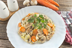 Risotto with mushrooms and vegetables in plate. On table Royalty Free Stock Image