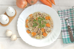 Risotto with mushrooms and vegetables in plate. On table Stock Images