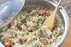 Risotto with mushrooms and vegetables in pot. On table Royalty Free Stock Photos